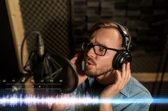 Homme avec des écouteurs chantant au studio d'enregistrement Images stock