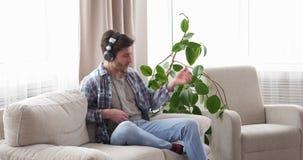 Homme avec des écouteurs jouant Air guitar sur le sofa banque de vidéos