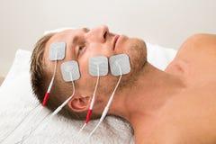 Homme avec des électrodes sur le visage Photos stock