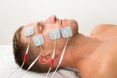 Homme avec des électrodes sur le visage Photographie stock