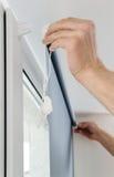 Homme avec des abat-jour de fenêtre Image stock