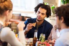 Homme avec des amis mangeant au restaurant Images stock