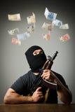 Homme avec des billets de banque d'arme à feu et d'euro Photographie stock libre de droits
