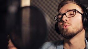 Homme avec des écouteurs chantant au studio d'enregistrement clips vidéos