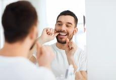 Homme avec des dents de nettoyage de fil dentaire à la salle de bains Photographie stock