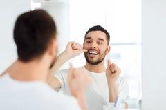 Homme avec des dents de nettoyage de fil dentaire à la salle de bains Photo libre de droits