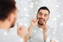 Homme avec des dents de nettoyage de fil dentaire à la salle de bains Photos stock