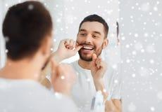 Homme avec des dents de nettoyage de fil dentaire à la salle de bains Photos libres de droits