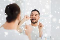 Homme avec des dents de nettoyage de fil dentaire à la salle de bains Image stock