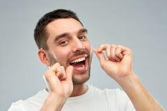Homme avec des dents de nettoyage de fil dentaire au-dessus de gris Photo libre de droits