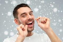 Homme avec des dents de nettoyage de fil dentaire au-dessus de neige Photographie stock