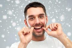 Homme avec des dents de nettoyage de fil dentaire au-dessus de neige Images libres de droits