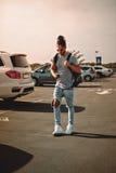 Homme avec des dreadlocks utilisant le téléphone sur un parking Photos stock