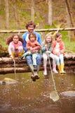 Homme avec des enfants sur le pont au centre d'activité en plein air Image libre de droits