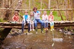 Homme avec des enfants sur le pont au centre d'activité en plein air Images libres de droits