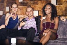Homme avec des femmes s'asseyant sur le divan dans la barre Photo stock