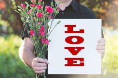 Homme avec des fleurs et le panneau-amour Photographie stock