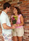 Homme avec des fleurs pour sa amie Photo stock