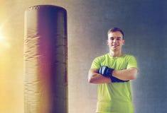Homme avec des gants de boxe et sac de sable dans le gymnase Photographie stock