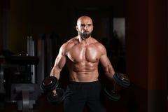 Homme avec des haltères exerçant des biceps Photographie stock libre de droits