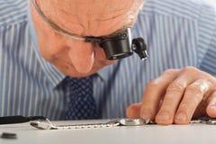Homme avec des loupes fixant la montre Images libres de droits