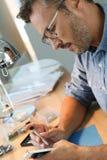 Homme avec des lunettes réparant le smartphone Photographie stock libre de droits