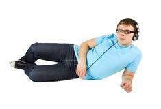 Homme avec des mensonges d'écouteurs d'isolement Photographie stock