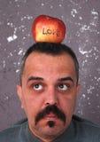Homme avec des moustaches montrant la pomme de Valentine Photos stock