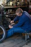 Homme avec des outils réparant la vieille moto dans l'atelier Photo libre de droits