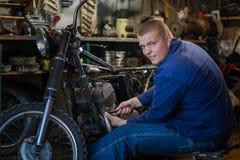 Homme avec des outils réparant la vieille moto dans l'atelier Photos libres de droits