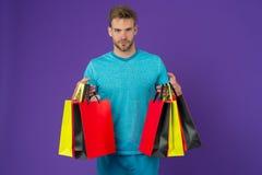 Homme avec des paniers sur le fond violet Macho avec les sacs en papier colorés Client de mode dans le T-shirt bleu occasionnel P Photographie stock