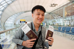 Homme avec des passeports de la Thaïlande dans des mains à l'aéroport Photographie stock libre de droits