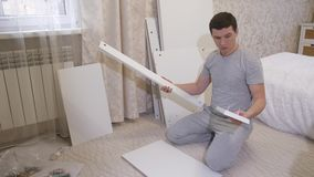 Homme avec des pièces de meubles banque de vidéos