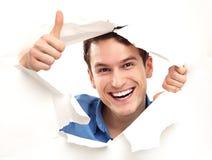 Homme avec des pouces piaulant vers le haut par le trou de papier Photos stock