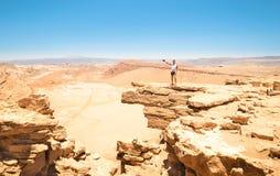 Homme avec des tatouages augmentant sur la formation de roche au désert d'Atacama Chili Image stock