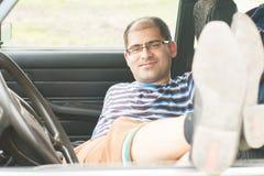 Homme avec des verres se reposant dans la voiture Photo stock