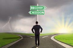 Homme avec deux choix de récession ou de relance Photos stock