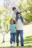 Homme avec deux enfants en bas âge exécutant le sourire Images stock