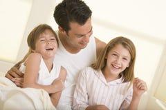 Homme avec deux enfants en bas âge s'asseyant dans le sourire de bâti Photos stock