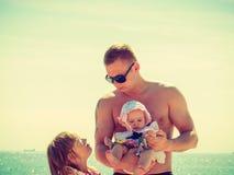 Homme avec deux enfants posant sur la côte Photographie stock libre de droits
