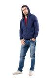 Homme avec du charme dans le pull molletonné à capuchon bleu avec des mains dans des poches regardant l'appareil-photo Photos stock
