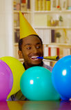 Homme avec du charme utilisant la chemise bleue et le chapeau se reposant par la table avec des ballons soufflant le klaxon de pa Photo libre de droits
