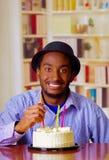 Homme avec du charme utilisant la chemise bleue et le chapeau se reposant par la table avec le gâteau d'anniversaire dans la boug Photo libre de droits