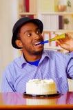 Homme avec du charme utilisant la chemise bleue et le chapeau se reposant par la table avec le gâteau d'anniversaire dans la célé Photos libres de droits