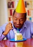 Homme avec du charme utilisant la chemise bleue et le chapeau se reposant par la table avec le morceau de gâteau dans l'avant, re Images libres de droits