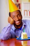 Homme avec du charme utilisant la chemise bleue et le chapeau se reposant par la table avec le morceau de gâteau dans l'avant, re Image stock