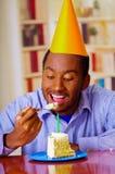 Homme avec du charme utilisant la chemise bleue et le chapeau se reposant par la table mangeant le morceau de gâteau dans l'avant Photo stock