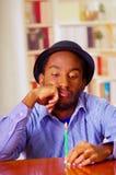 Homme avec du charme utilisant la chemise bleue et le chapeau se reposant par le cadeau d'anniversaire d'ouverture de table, rega Photographie stock
