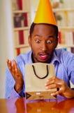 Homme avec du charme utilisant la chemise bleue et le chapeau se reposant par le cadeau d'anniversaire d'ouverture de table, rega Photos stock