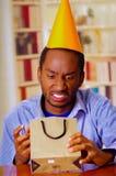 Homme avec du charme utilisant la chemise bleue et le chapeau se reposant par le cadeau d'anniversaire d'ouverture de table, rega Photos libres de droits